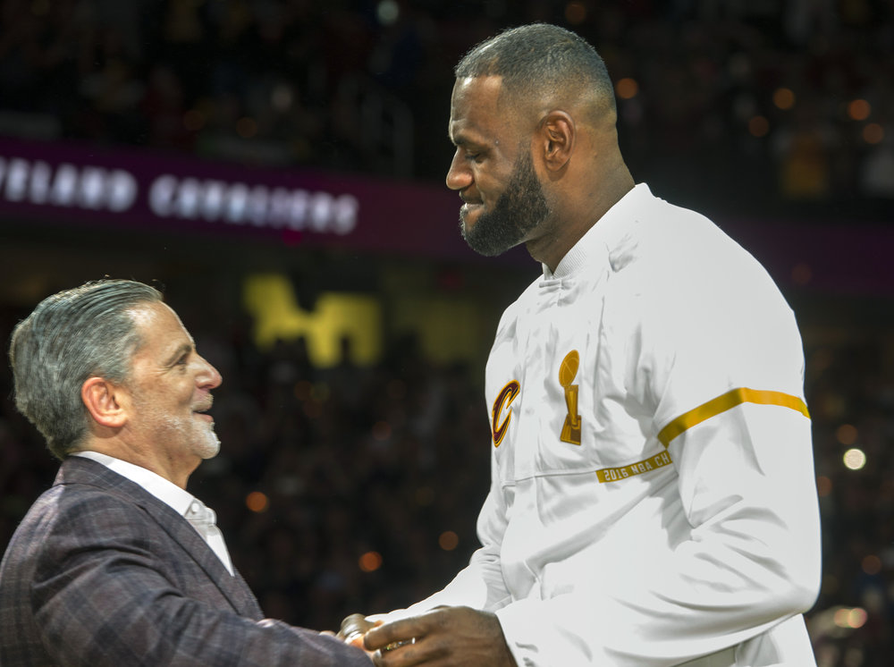 Cleveland Cavaliers' LeBron James accepts his NBA championship ring from Cavaliers owner Dan Gilbert before a basketball game against the New York Knicks in Cleveland, Tuesday, Oct. 25, 2016. (Phil Long/AP Photo)