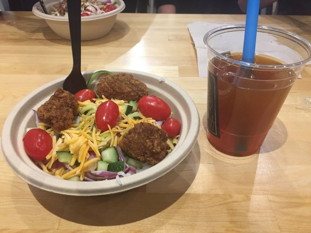A large rice bowl and added cucumbers, tomatoes, scallions, red onions and zucchini noodles to go with fried chicken, cheese and garlic ponzu sauce to top it all off. And a mango tea bubble tea with strawberry pops to finish off the meal. (Chris Hanna/The Daily Campus)