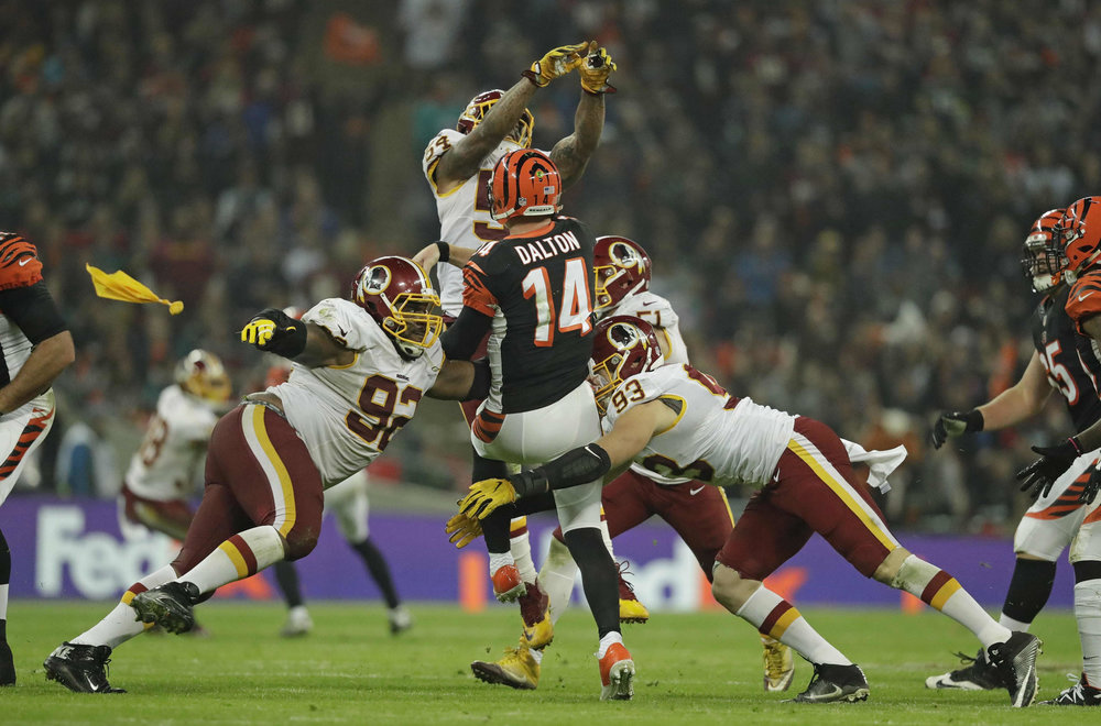 Cincinnati Bengals quarterback Andy Dalton (14), centre, is tackled after managing to throw the ball away during the team's 27-27 tie against Washington Redskins at Wembley Stadium in London, Sunday Oct. 30, 2016. (Matt Dunham/AP)
