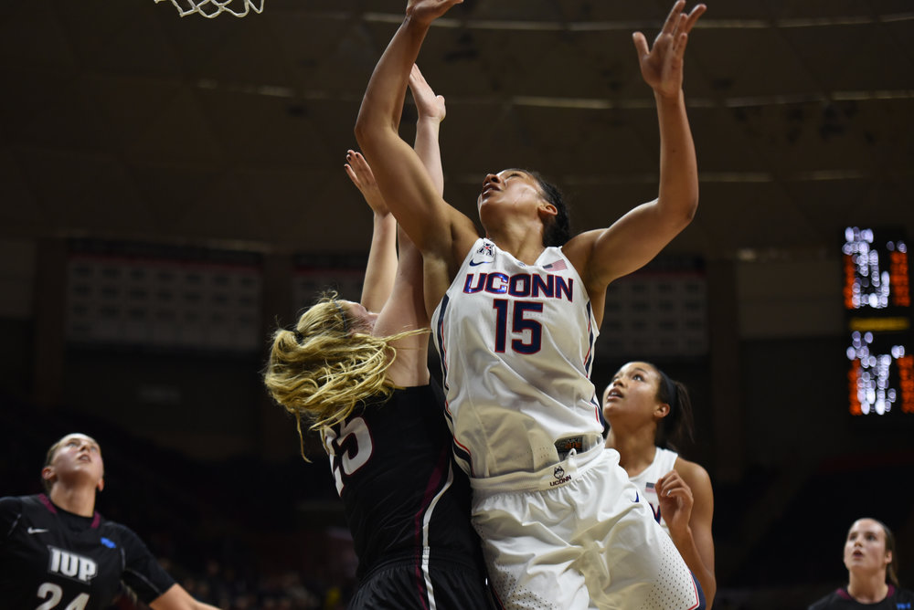 Junior guard Gabby Williams (15) jumps for a rebound during the Huskies 111-39 victory over the Indiana University of Pennsylvania Crimson Hawks in the team's exhibition opener. Williams scored 22 points for the team. (Charlotte Lao/The Daily Campus)