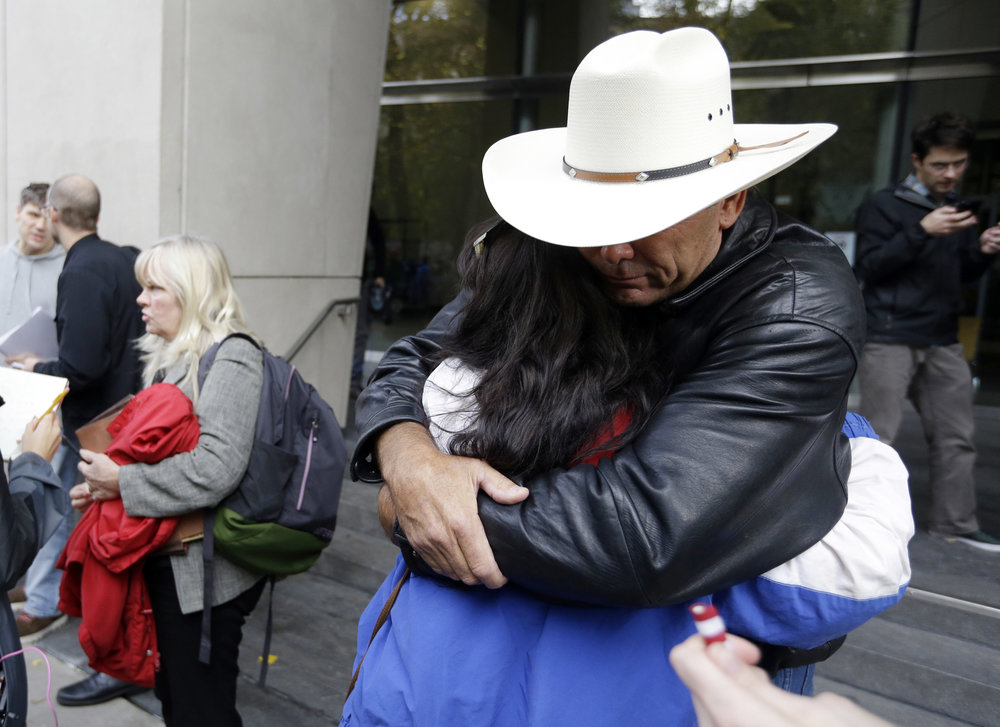 Defendant Shawna Cox speaks at left as supporters hug outside federal court in Portland, Ore., Thursday, Oct. 27, 2016. A jury exonerated brothers Ammon and Ryan Bundy and five others of conspiring to impede federal workers from their jobs at the Malheur National Wildlife Refuge. (Don Ryan/AP)