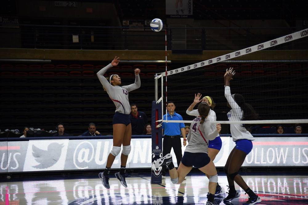 UConn junior Tosin Adeniyi (#13) goes up to spike the ball as sophomore Emma Turner (#4) looks on in a game against Memphis on Oct. 30, 2016. The Huskies won three sets to none. (Charlotte Lao/The Daily Campus)
