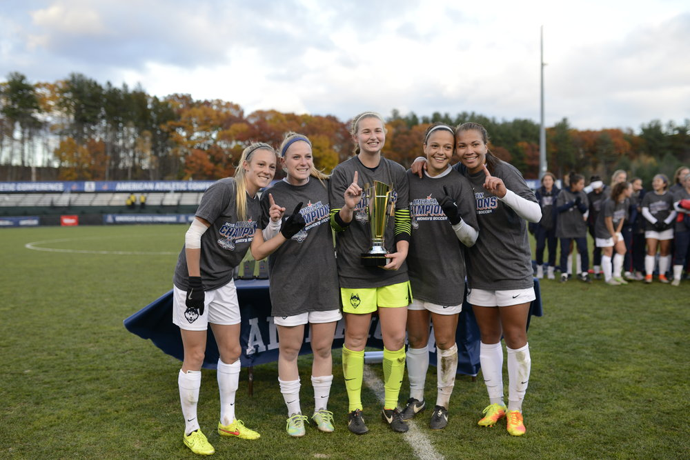 From left to right: Seniors Rachel Hill, Maddie Damm, Emily Armstrong, Stephanie Ribeiro and Toriana Patterson pose with the American Athletic Conference championship trophy on Sunday, Nov. 6 at Joseph J. Morrone Stadium. The Huskies defeated SMU 1-0 to capture the title. (Jason Jiang/The Daily Campus)