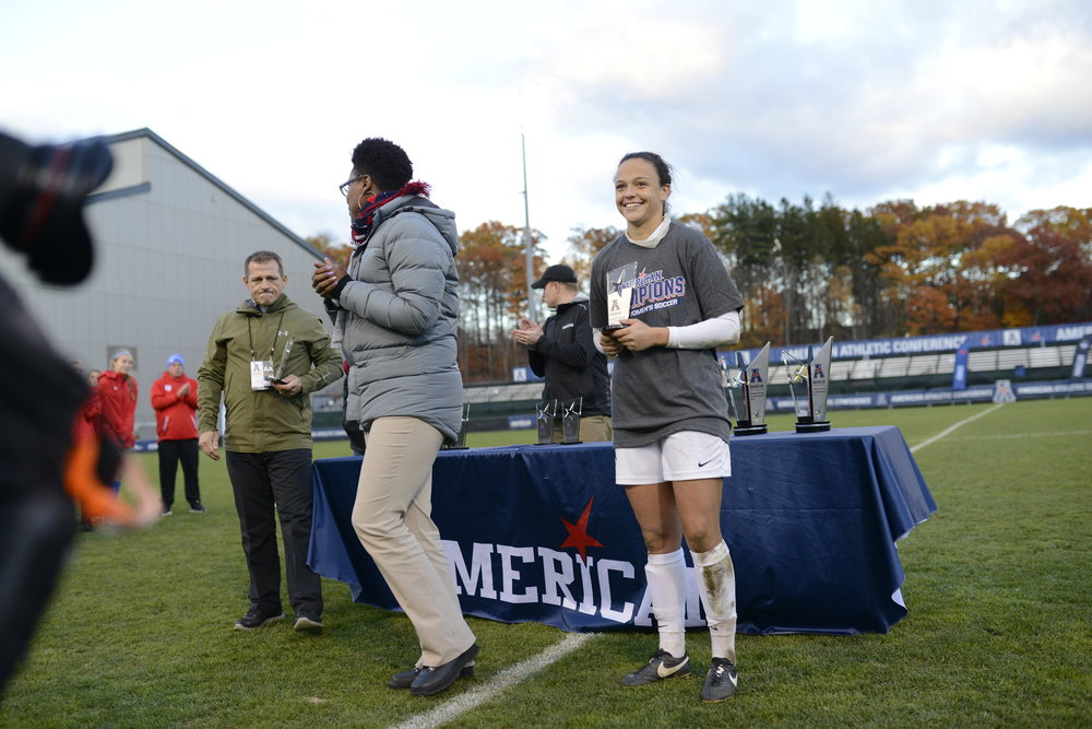 Redshirt senior forward Stephanie Ribeiro accepts her trophy following a 1-0 win over SMU to win the American Athletic Conference title on Sunday, Nov. 6 at Joseph J. Morrone Stadium. Ribeiro was named to the All-Tournament team following the Huskies' victory. (Jason Jiang/The Daily Campus)