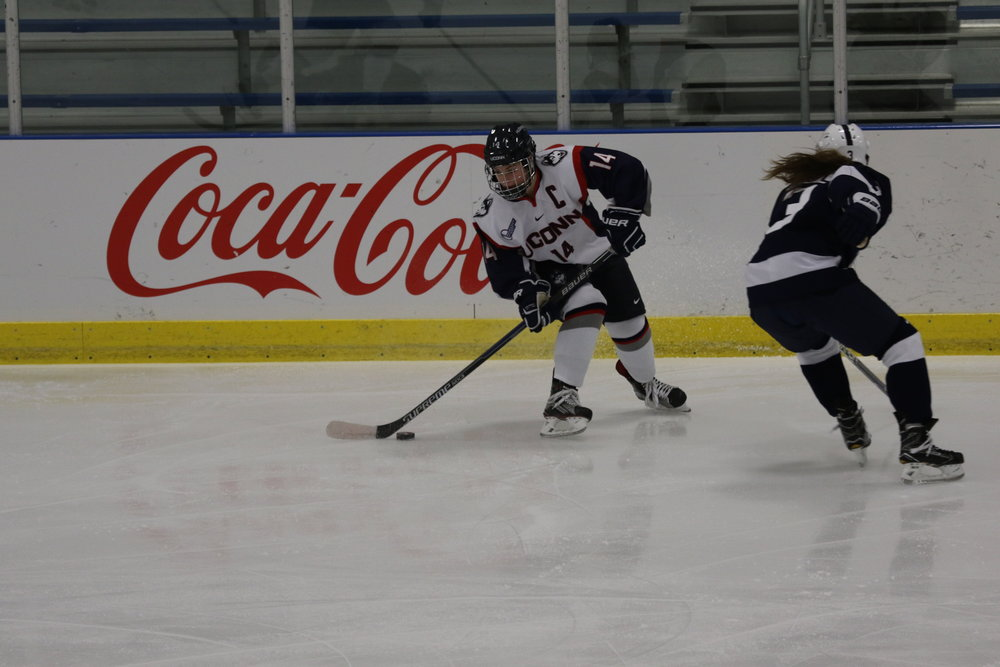 UConn's Justine Fredette (14) skates around a Penn State defender in a game on Saturday Oct. 22 at the Freitas Ice Forum. The Huskies won 4-2. (Ruohan Li/The Daily Campus)
