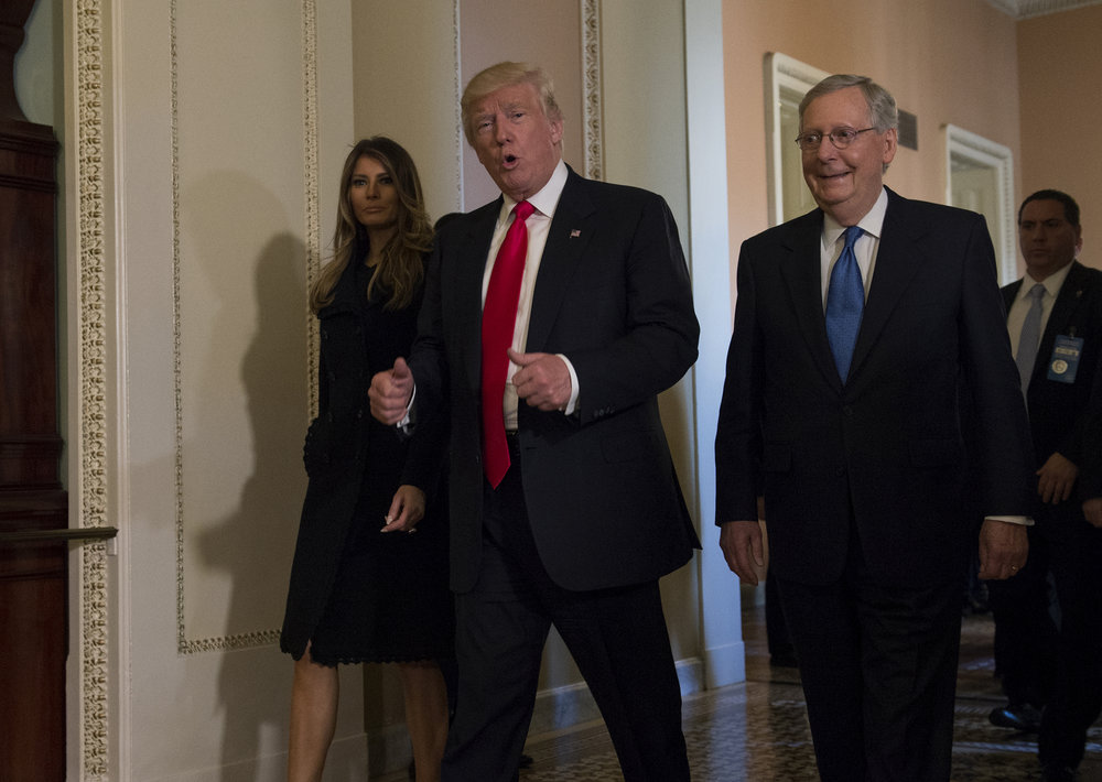 President-elect Donald Trump, accompanied by his wife Melania, and Senate Majority Leader Mitch McConnell of Ky., gestures while walking on Capitol Hill in Washington, Thursday, Nov. 10, 2016, after meeting. (Molly Riley/AP)