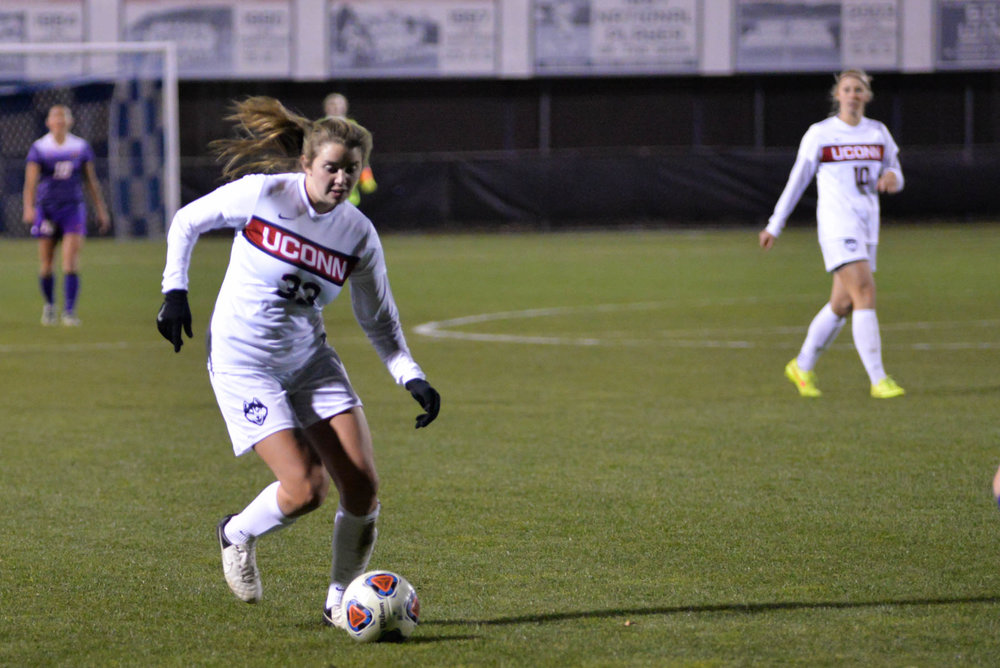 Midfielder Sabrina Toole (33) drives the ball down the field during the Huskies 4-2 victory over the Great Danes during the first round of the NCAA tournament Saturday night at Morrone Stadium. (Amar Batra/The Daily Campus)