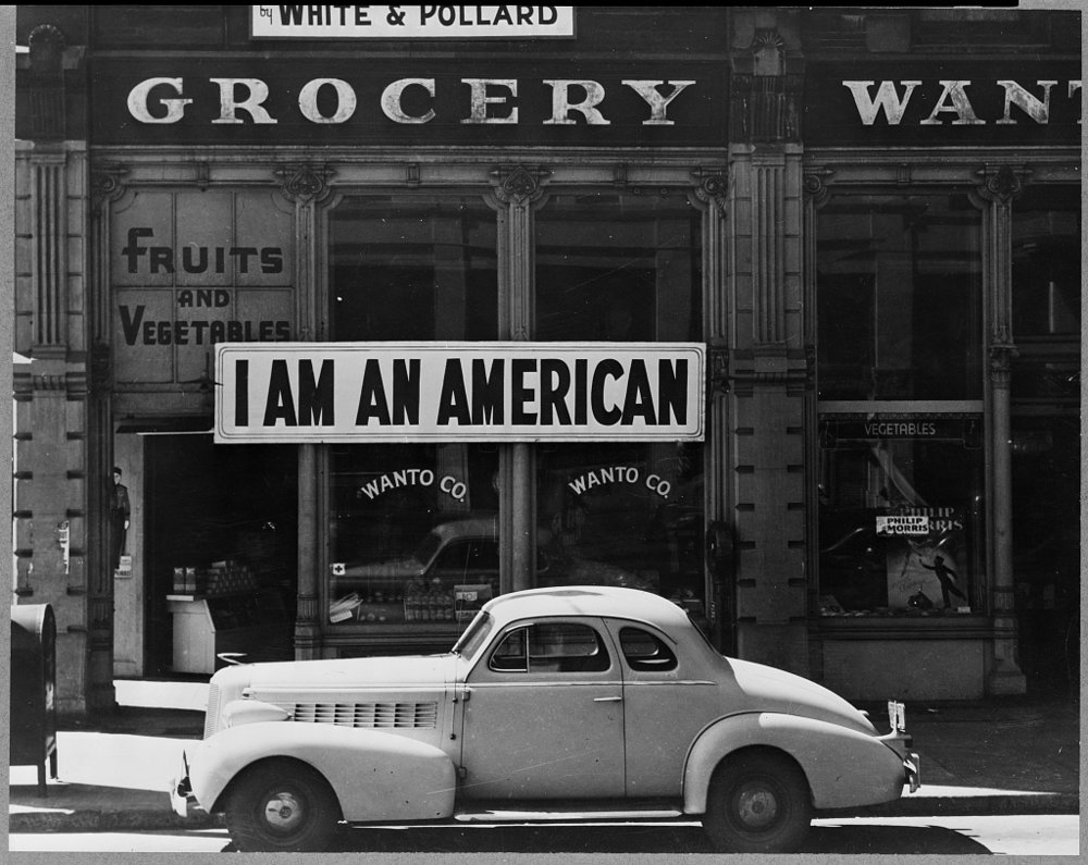 "Oakland, Calif., Mar. 1942. A large sign reading ""I am an American"" placed in the window of a store, at 13th and Franklin streets, on December 8, the day after Pearl Harbor. The store was closed following orders to persons of Japanese descent to evacuate from certain West Coast areas. (Library of Congress)"