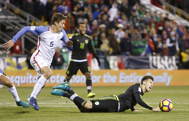 Mexico's Hector Herrera, right, falls to the ground as United States' Matt Besler looks for the ball during the second half of a World Cup qualifying soccer match Friday, Nov. 11, 2016, in Columbus, Ohio. (Jay LaPrete/AP Photo)