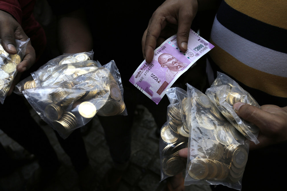 An Indian shows a new Rupees 2000 currency note and coins of Rupees 10 he received in exchange of discontinued currency outside the Reserve Bank of India in Kolkata, India, Wednesday, Nov. 16, 2016. India announced a that it was withdrawing 500 and 1,000 rupee notes as legal tender to fight corruption and tax evasion. (Bikas Das/AP)