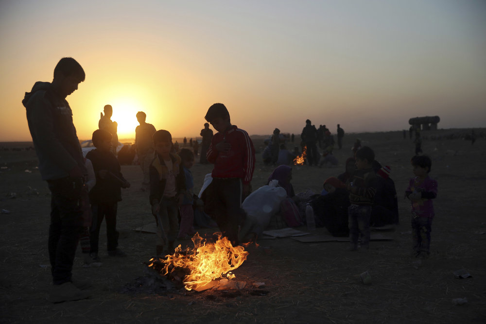 Iraqis who fled the fighting between Iraqi forces and Islamic State militants, gather around flames to warm themselves from the cold wind, as they wait to cross to the Kurdish controlled area, in the Nineveh plain, northeast of Mosul, Thursday, Nov. 17, 2016. (Hussein Malla/AP)