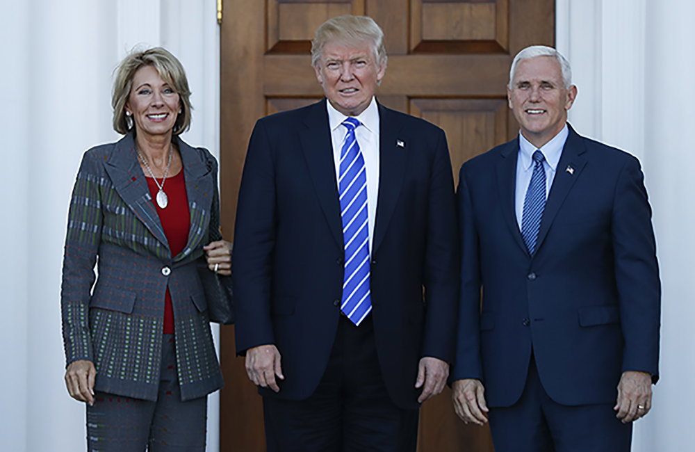 President-elect Donald Trump, Vice President-elect Mike Pence and Betsy DeVos pose for photographs at Trump National Golf Club Bedminster clubhouse in Bedminster, N.J. Trump has chosen charter school advocate DeVos as Education Secretary in his administration. (Carolyn Kaster/AP)