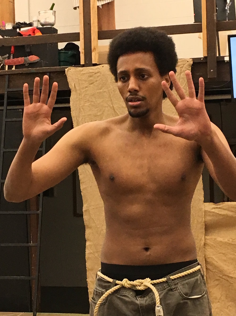 Sam Kebede puts his hands up pressing against an invisible wall, reminiscent of the hands up don't shoot pose and chant seen and heard in Ferguson, MO. (Matthew Gilbert/The Daily Campus)