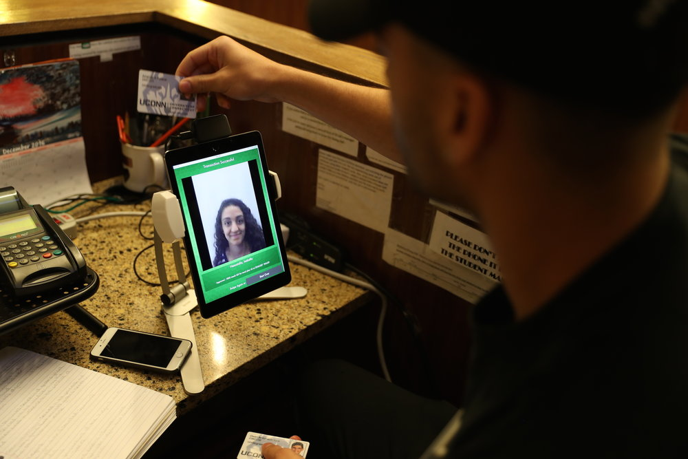 Wednesday, Dec. 7, 2016 - An employee in McMahon dining hall swipes a student's OneCard ID through the new tablet-based swiping system that is being implemented throughout all eight dining halls. (Owen Bonaventura/The Daily Campus)