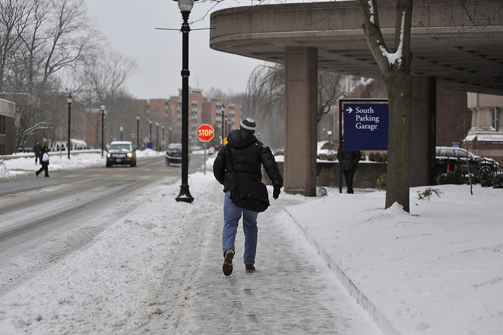 In this file photo from February 2016, a student walks in front of Gampel Pavillion. Finals before 10 a.m. on Monday, Dec. 12, 2016 have been postponed ahead of a predicted snowstorm. (Jason Jiang/Daily Campus)
