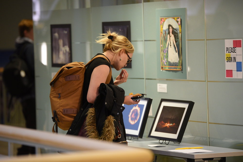 A UConn student looks at student art exhibitions in the Wilbur Cross second floor. This semesterly event provides UConn students the opportunity to showcase their artistic talent in a professional juried exhibition. (Zhelun Lang/The Daily Campus)