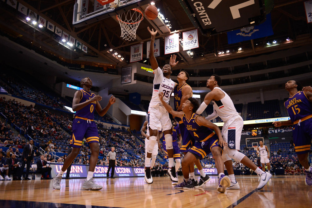Amida Brimah floats a basket over a group of ECU defenders during the Huskies 72-65 victory over the Pirates on Sunday, Jan. 22, 2016. (Jason Jiang/The Daily Campus)