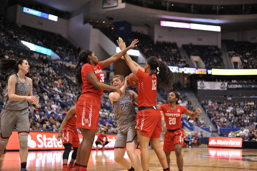 Freshman forward Kyla Irwin fights her way through Houston defenders in the paint. (Jason Jiang/The Daily Campus)
