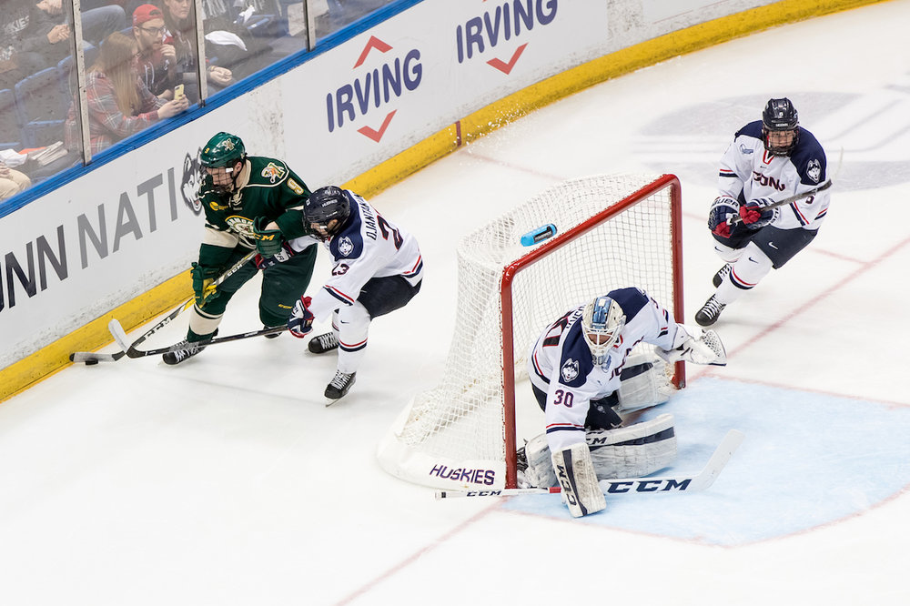 Freshman goalie Adam Huska (#30) minds the net while juniors Kasperi Ojantakanen (#23) and David Drake (#5) defend against Vermont's sophomore Brian Bowen (#9) in Friday's 3-1 win at the XL Center. (Owen Bonaventura/The Daily Campus)