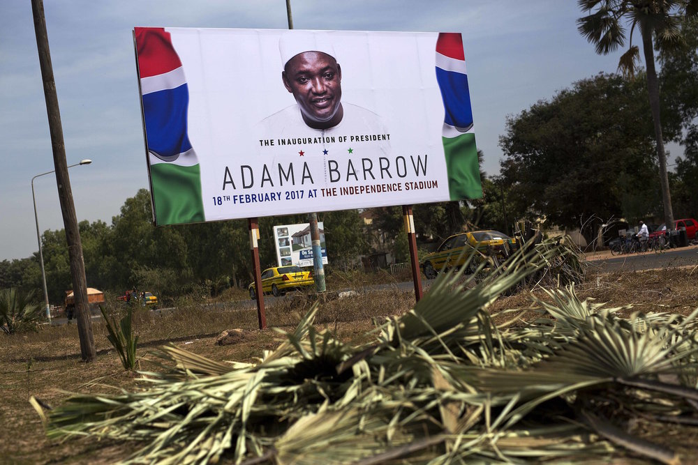A billboard calling for the inauguration of Adam Barrow as president in Feb. 18 is set on the side of a road in Serrukunda, Gambia, Friday Jan. 27, 2017. Hundreds of thousands turned out Thursday to greet President Adama Barrow, a week after he took the oath of office in neighboring Senegal. (Jerome Delay/AP Exchange)