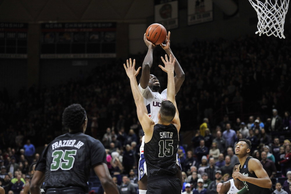 Amida Brimah gets up for a layup over Tulane's Ryan Smith in Saturday's win over the Green Wave at Gampel Pavilion. (Jason Jiang/The Daily Campus)