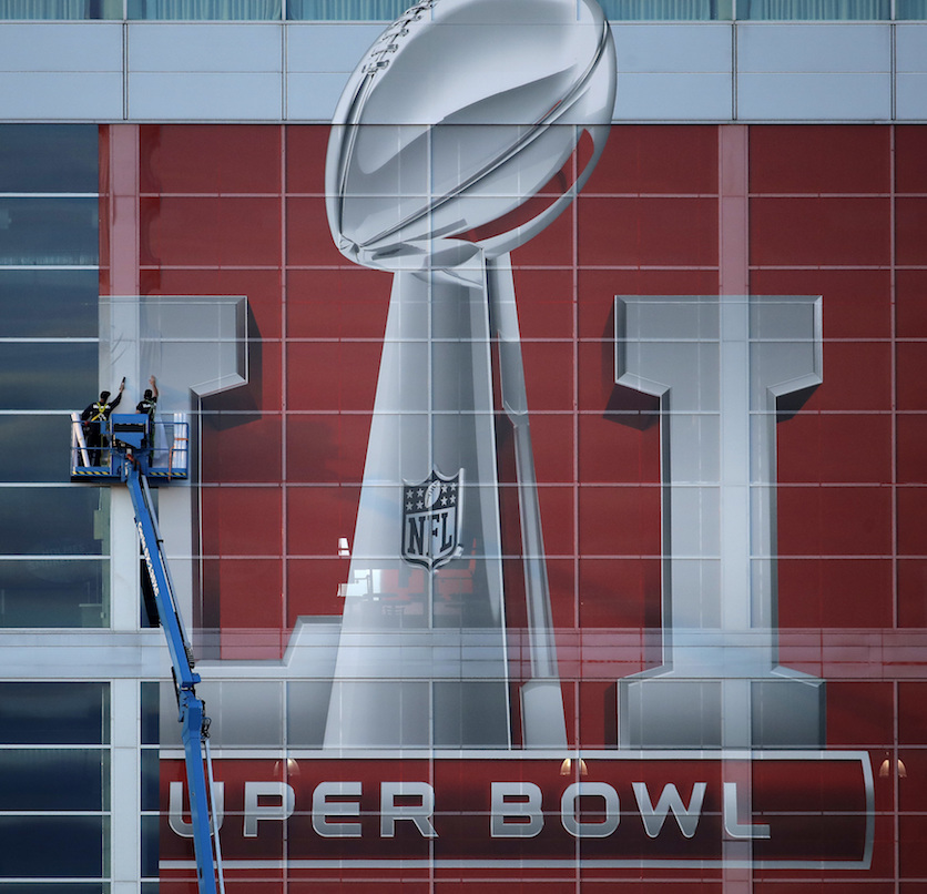 Workers attach a sign to the front of NRG Stadium as preparations continue for the NFL  Super   Bowl  51 football game Sunday, Jan. 29, 2017, in Houston. (AP Photo/Charlie Riedel)