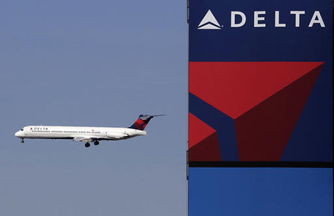 In this Saturday, April 6, 2013, file photo, a Delta Airlines jet flies past the company's billboard at Citi Field, in New York. A Massachusetts man who authorities say assaulted a Muslim airline employee at New York's Kennedy Airport is facing hate crime charges.  (Mark Lennihan/AP)