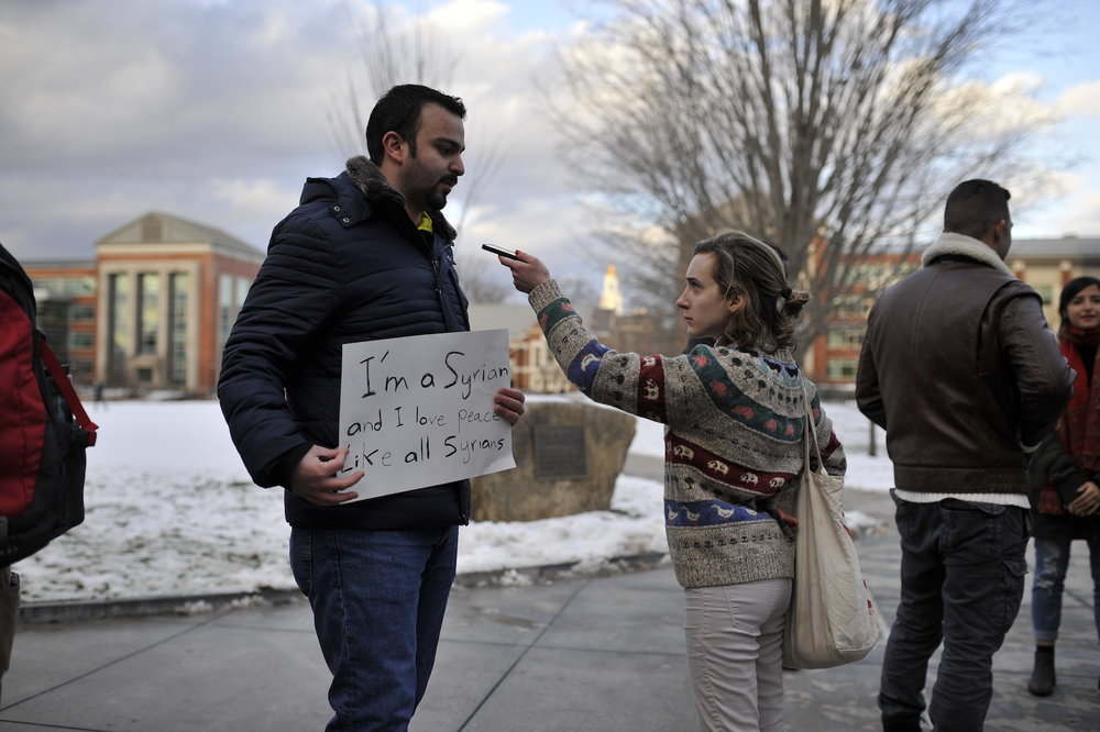 "UConn journalism student Hannah Dickison interviews a Syrian man attending the rally who's sign reads ""I'm a Syrian and I love peace like all Syrians."" (Jason Jiang/The Daily Campus)"