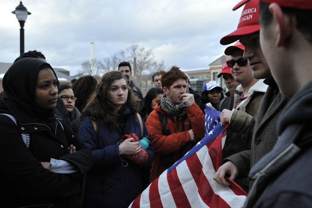 "Rally attendees and Trump supporters debate on the steps outside the Student Union. The Trump supporters attended the rally with an American Flag and ""Make America Great Again"" hats. (Jason Jiang/The Daily Campus)"
