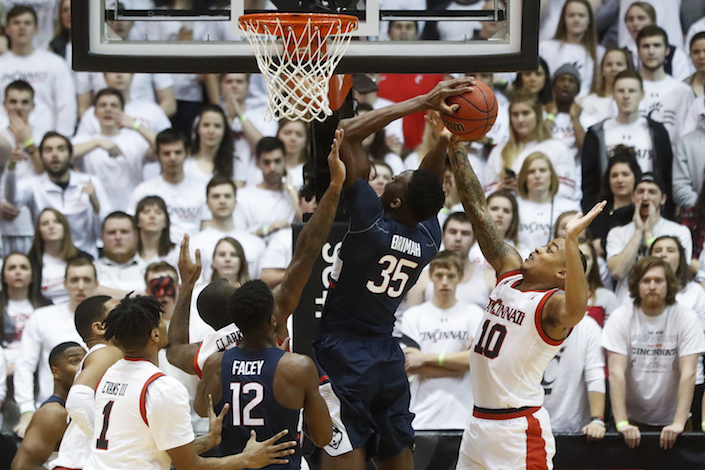 Cincinnati's Troy Caupain (10) blocks a shot by Connecticut's Amida Brimah (35) in the first half of an NCAA college basketball game, Saturday, Feb. 4, 2017, in Cincinnati. (AP Photo/John Minchillo)