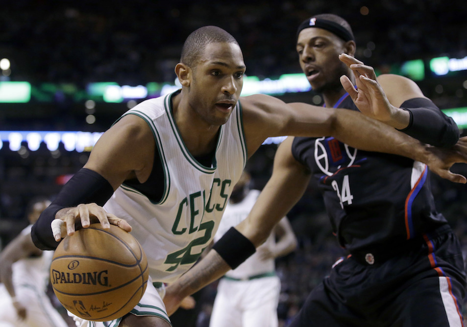 Boston Celtics center Al Horford, left, of the Dominican Republic, looks for an opening around Los Angeles Clippers forward Paul Pierce (34) in the first half of an NBA basketball game, Sunday, Feb. 5, 2017, in Boston. (AP Photo/Steven Senne)