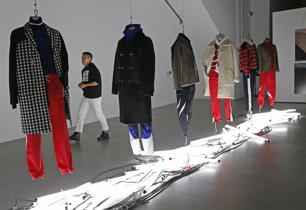A stylist walks through the Tim Coppens capsule collection moments before the show's opening during Men's Fashion Week, Thursday, Feb. 2, 2017, in New York. (AP Photo/Kathy Willens)