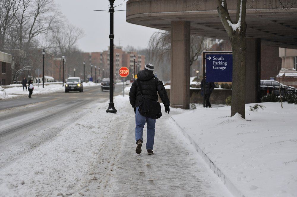 A student walks across campus on February 8th, 2017 during a snowstorm. (Jason Jiang/The Daily Campus)