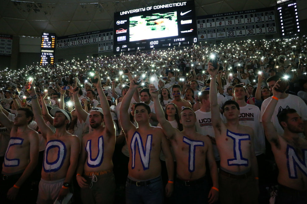 Students hold their cell phone flashlights for the national anthem. (Jackson Haigis/The Daily Campus)
