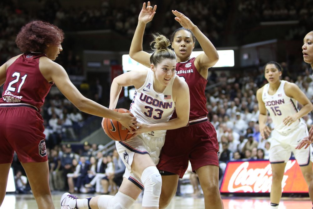 Katie Lou Samuelson attempts to evade two USC defenders in the first half of Monday night's game at Gampel Pavilion. (Jackson Haigis/The Daily Campus)