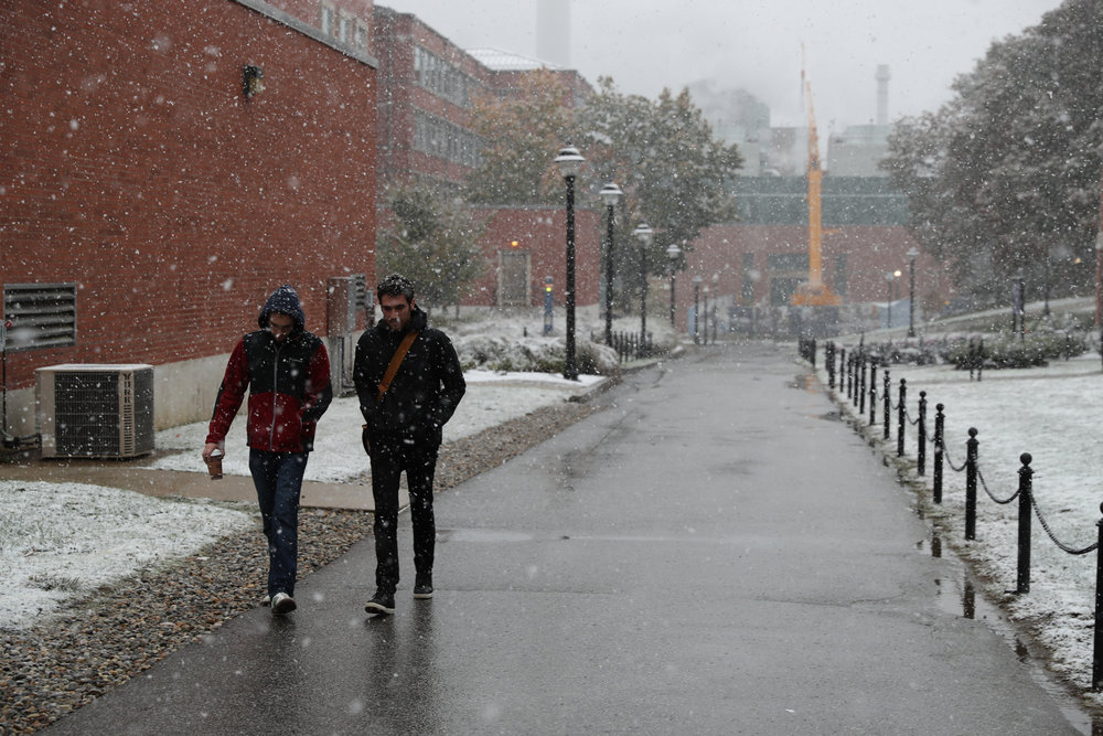 Two students brave the cold weather that is UConn in winter and walk to class. (Owen Bonaventura/The Daily Campus)