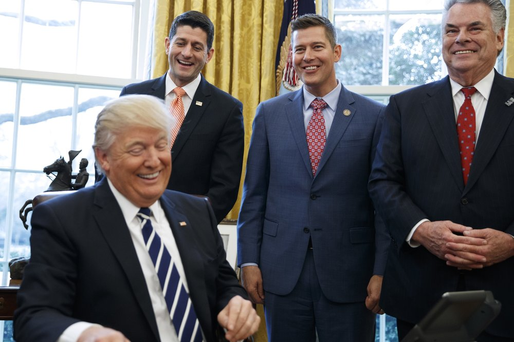 President Donald Trump, jokes with, from left, House Speaker Paul Ryan of Wis., Rep. Sean Duffy, R-Wis., and Rep. Peter King, R-N.Y. in the Oval Office of the White House in Washington, Tuesday, Feb. 14, 2017, after the president signed House Joint Resolution 41. (Evan Vucci/AP Photo)