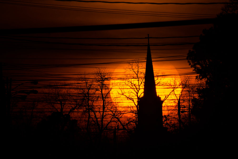 In this Tuesday, Feb. 14, 2017 photo, the sun sets behind a church steeple in Montgomery, Ala. (Albert Cesare/AP)