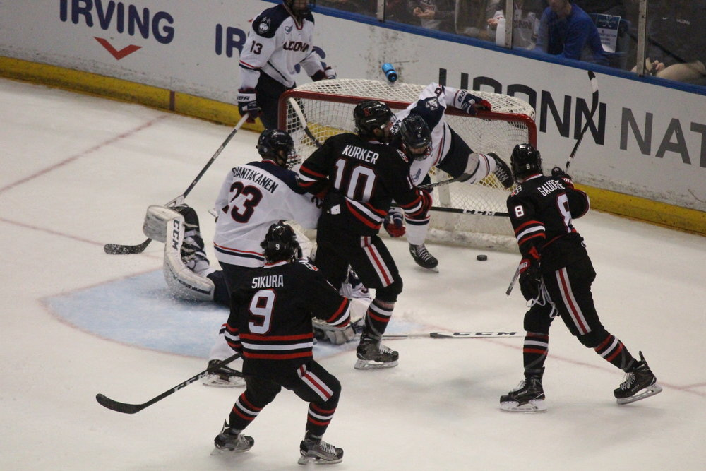 Northeastern's Dylan Sakura (#9), Sam Kurker (#10), and Adam Gaudette (#8) celebrate a goal. UConn forward Kasperi Ojantakanen (#23) looks on from the crease as goalie Adam Huska's (#30) diving effort wasn't enough. (Mustafe Mussa/The Daily Campus)