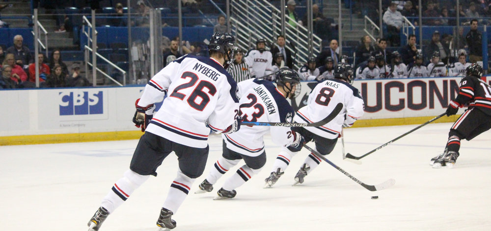 Philip Nyberg (#26), Kasperi Ojantakanen (#23) and Spencer Naas (#8) take the puck up in UConn's loss to Northeastern on Friday night at the XL Center. (Mustafe Mussa/The Daily Campus)
