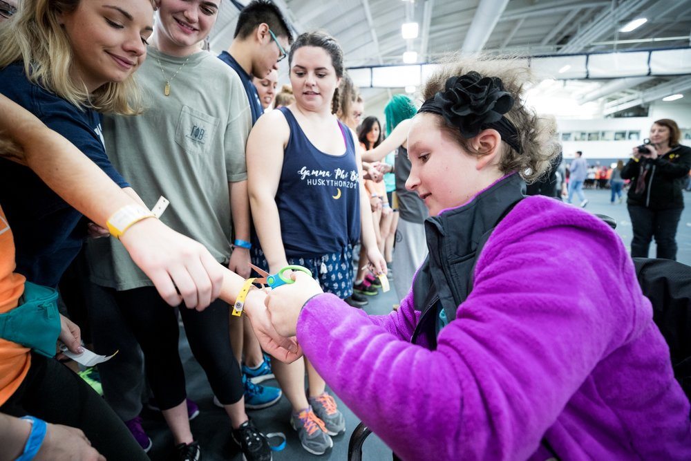 A miracle child removes a HuskyTHON participant's hospital band to symbolize the day when no child will need to go to the hospital. (Owen Bonaventura/The Daily Campus)