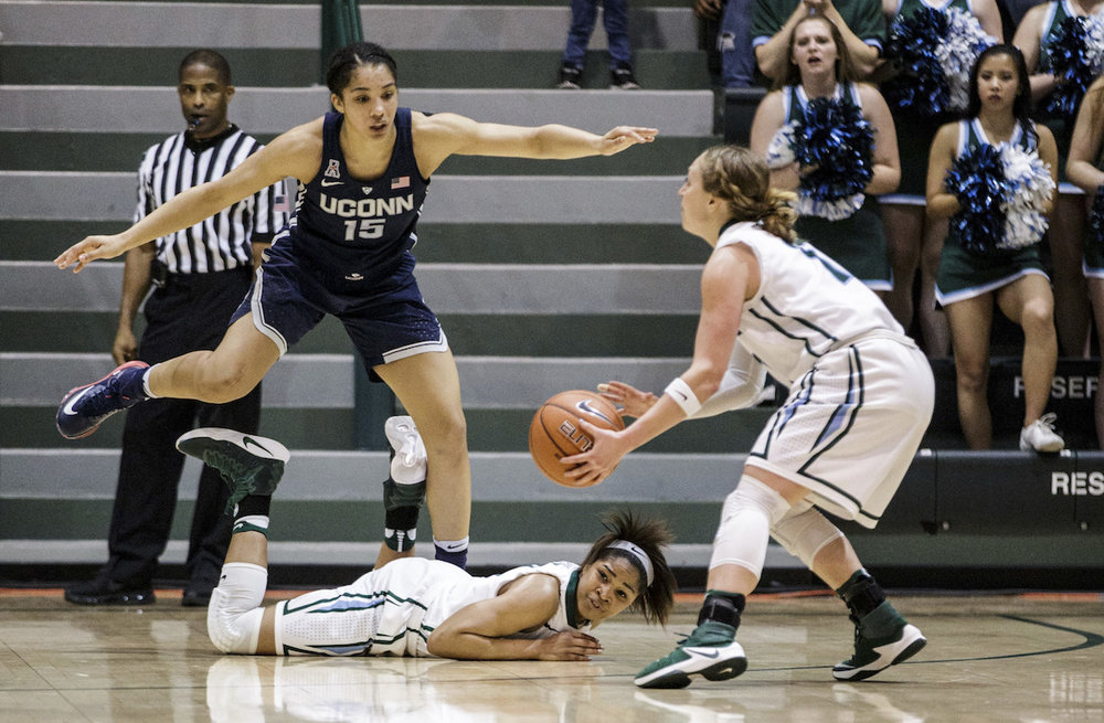 Connecticut guard Gabby Williams (15) jumps over Tulane guard Kolby Morgan, center, as Tulane guard Leslie Vorpahl, right, gets the ball during the second half of an NCAA college basketball game in New Orleans, Saturday, Feb. 18, 2017. (AP Photo/Sophia Germer)