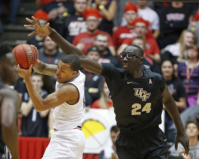 Cincinnati guard Troy Caupain, left, grabs a rebound in front of Central Florida center Tacko Fall (24) during the first half of an NCAA college basketball game, Wednesday, Feb. 8, 2017, in Cincinnati. (AP Photo/Gary Landers)