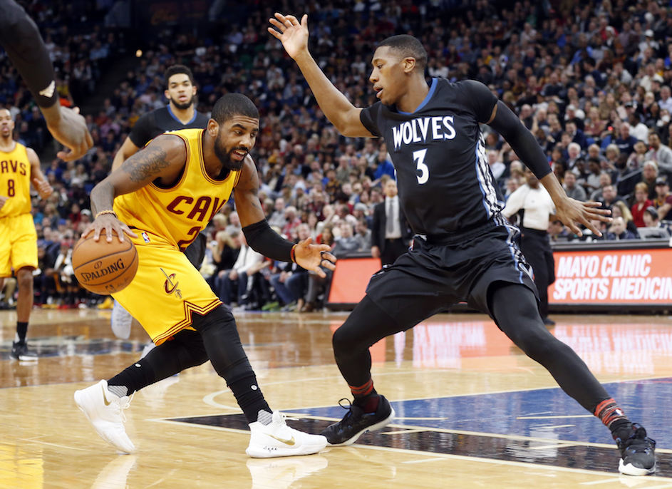 Cleveland Cavaliers' Kyrie Irving, left, keeps an eye on Minnesota Timberwolves' Kris Dunn during the second half of an NBA basketball game Tuesday, Feb. 14, 2017, in Minneapolis. The Cavaliers won 116-108. Irving and LeBron James each scored 25 points to lead their team in scoring. (AP Photo/Jim Mone)