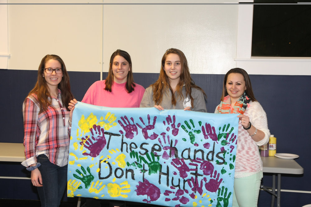 Students pose with a banner created during the Sex and Candy event Tuesday night in Shippee Residence Hall. (Ginikachi Anosike/The Daily Campus)
