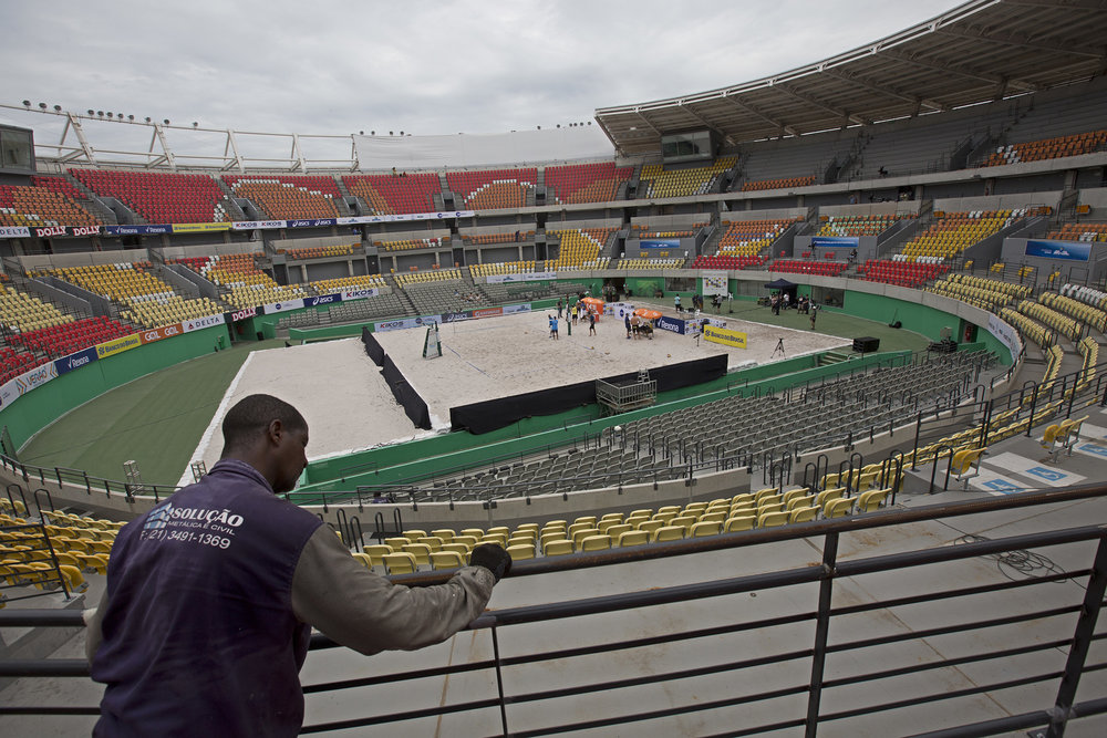In this Feb. 4, 2017 photo, a worker paints a fence at the Olympic Tennis Center inside Olympic Park in Rio de Janeiro, Brazil. This venue is one of four permanent arenas being run by the federal government, and was used for a one-day beach volleyball tournament, in a city with endless sand and beaches. (Silvia Izquierdo/AP)