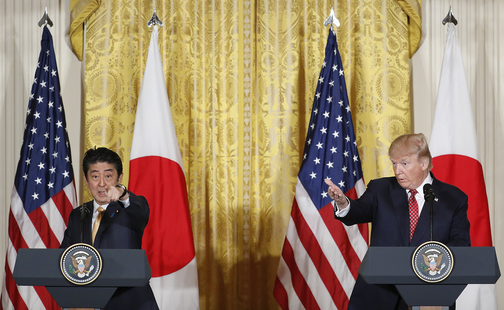 President Donald Trump and Japanese Prime Minister Shinzo Abe both gesture as they take questions from members of the media during their joint news conference in the East Room of the White House in Washington, Friday, Feb. 10, 2017. (Pablo Martinez Monsivais/ AP)