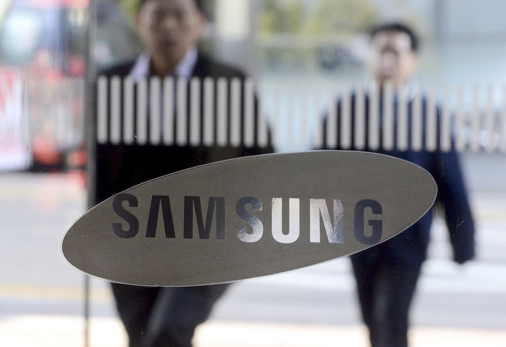 Employees walk past a logo of Samsung Group at its headquarters in Seoul, South Korea, Friday, Feb. 17, 2017. (Kwon Hyun-goo/Newsis/AP)