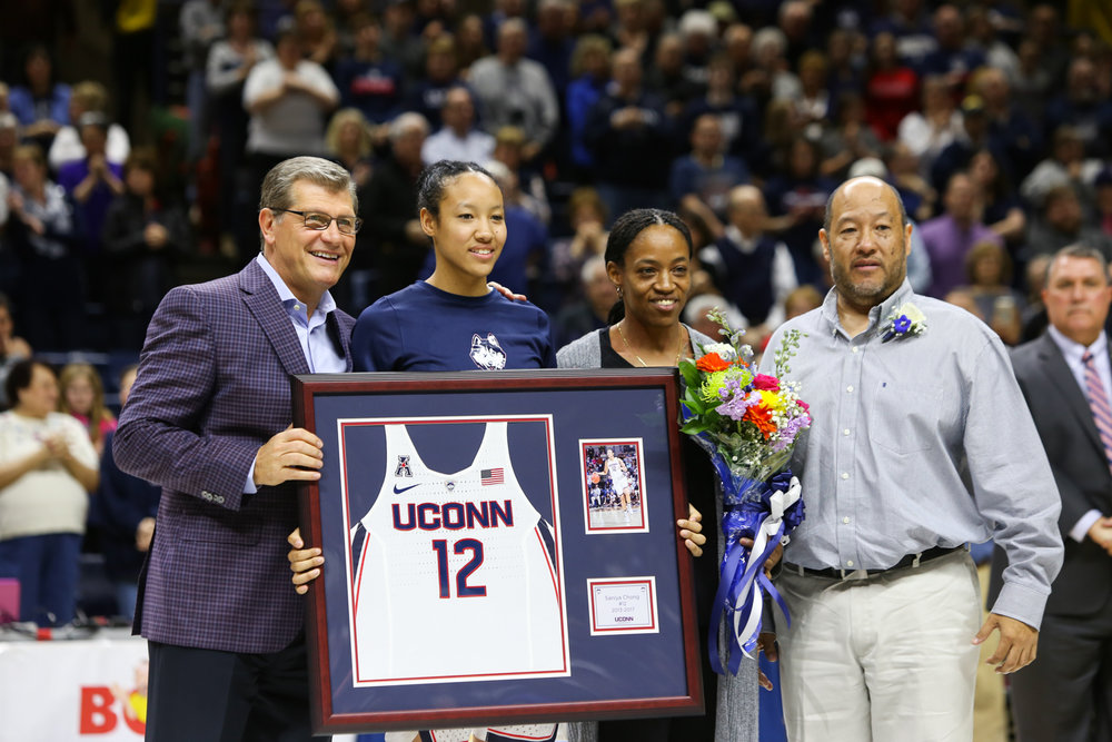 UConn senior Saniya Chong, pictured with her parents and head coach Geno Auriemma, is honored before Saturday afternoon's game as part of the pregame senior day ceremony. (Jackson Haigis/The Daily Campus)