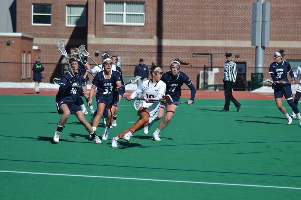 Grace Nolan (#10) runs through a group of UNH defenders in the Huskies' victory. Nolan had five goals and three assists on the day. (Olivia Stenger/The Daily Campus)